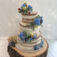 Naked wedding cake with blue flowers