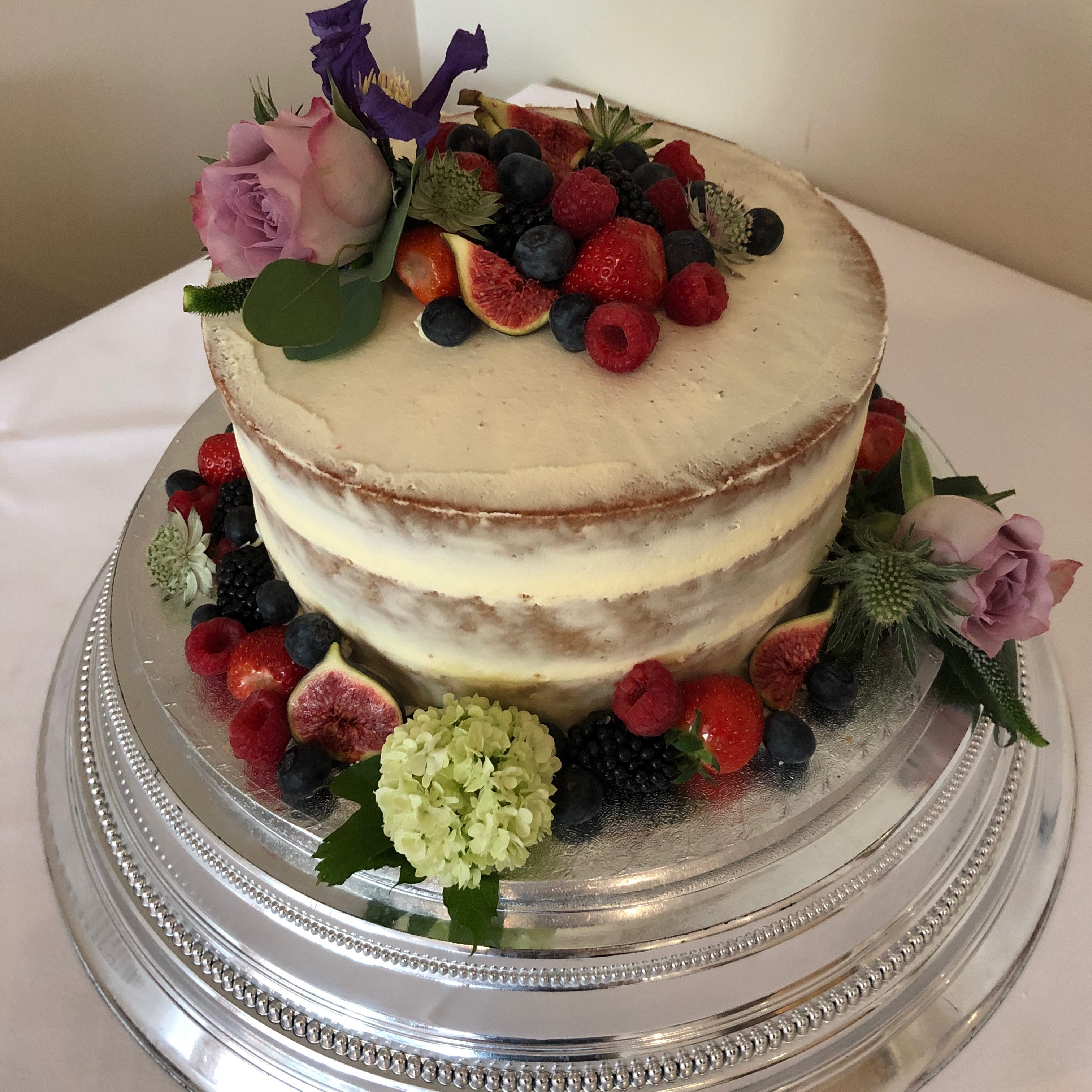 Semi-naked buttercream wedding cake with fresh fruit & flowers
