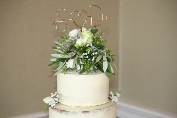 Semi-naked wedding cake flower topper close-up