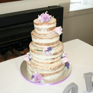 Semi-naked wedding cake decorated with sugar flowers