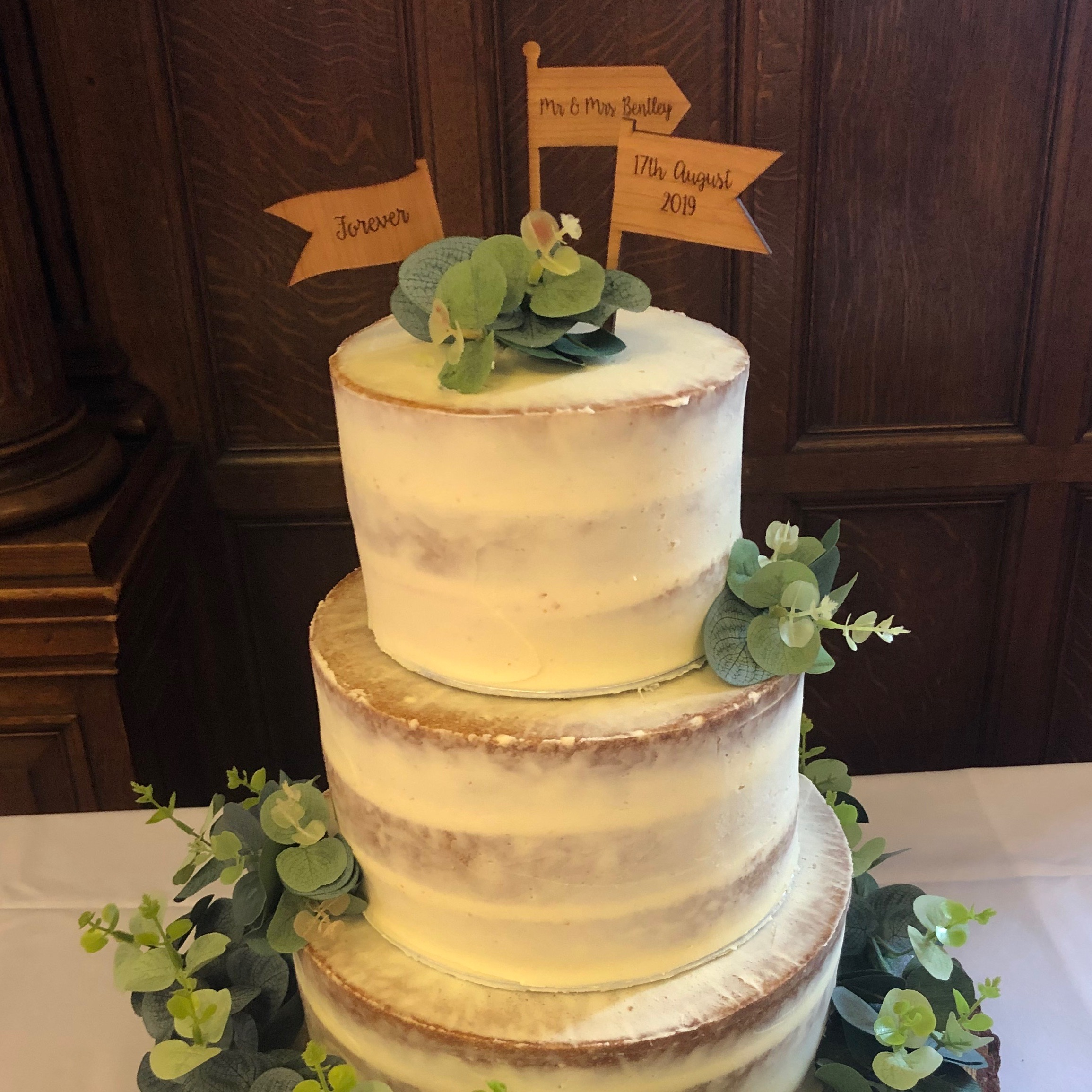 Semi-naked wedding cake with eucalyptus leaves