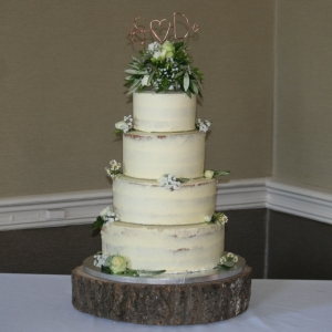 4 tier semi-naked cake with green/cream flowers & topper